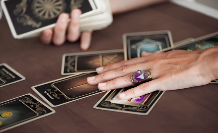 woman resting her hands on a tarot spread
